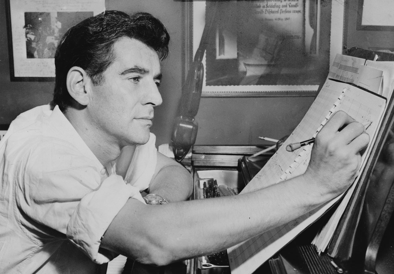 a black and white of bernstein seated at a piano, making annotations on a piece of sheet music