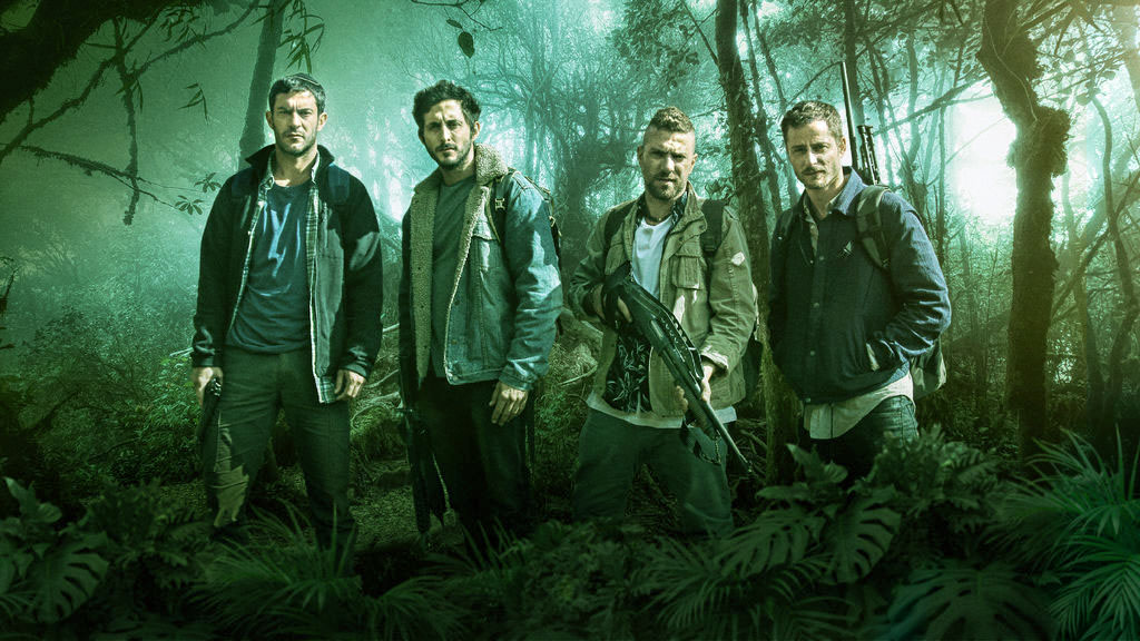 four men with guns stand in a forest looking very dramatic