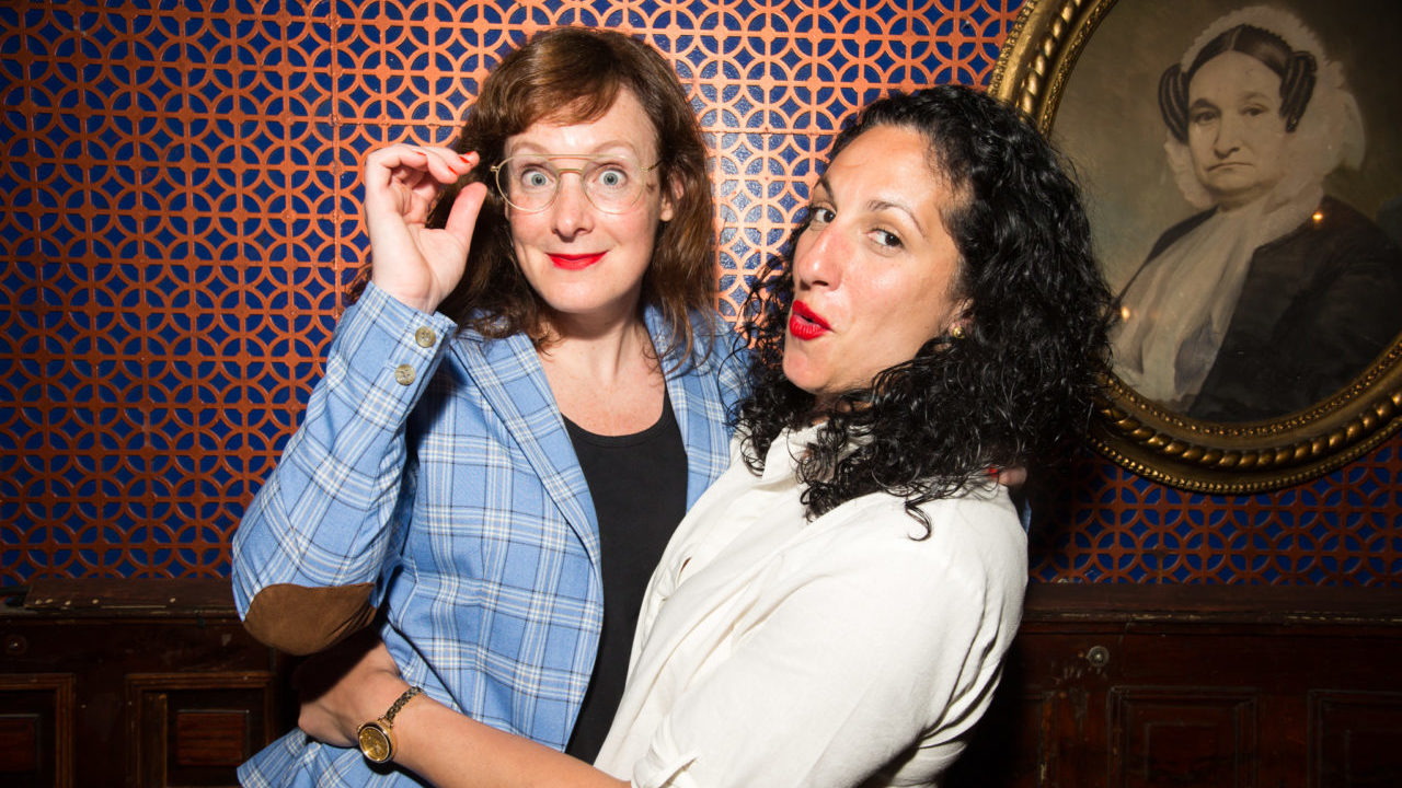 a red-haired woman with glasses and a woman with dark curly hair embrace and make faces for the comera