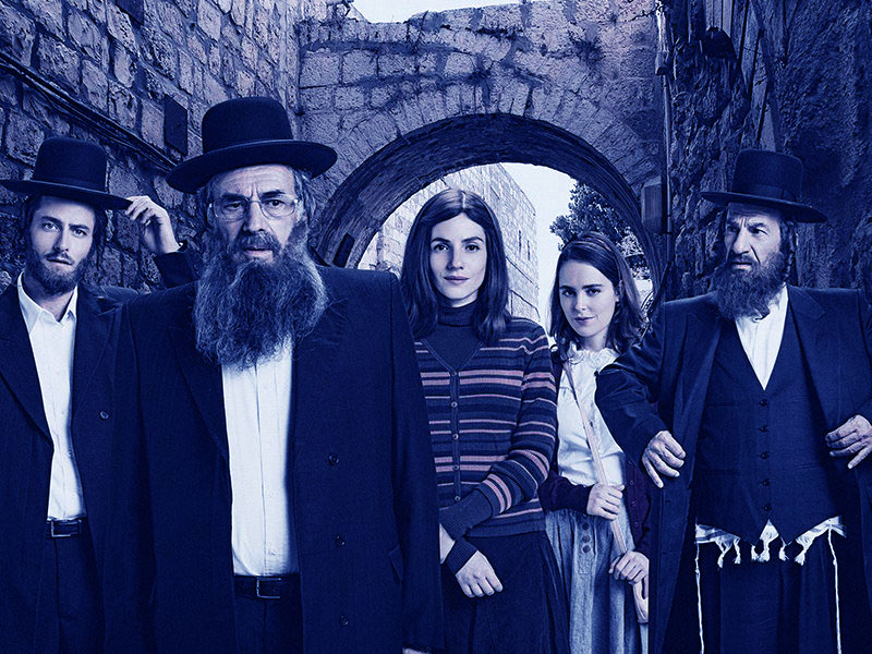 three men (one young, two older) in black hat Haredi outfits, and two modestly dressed young women