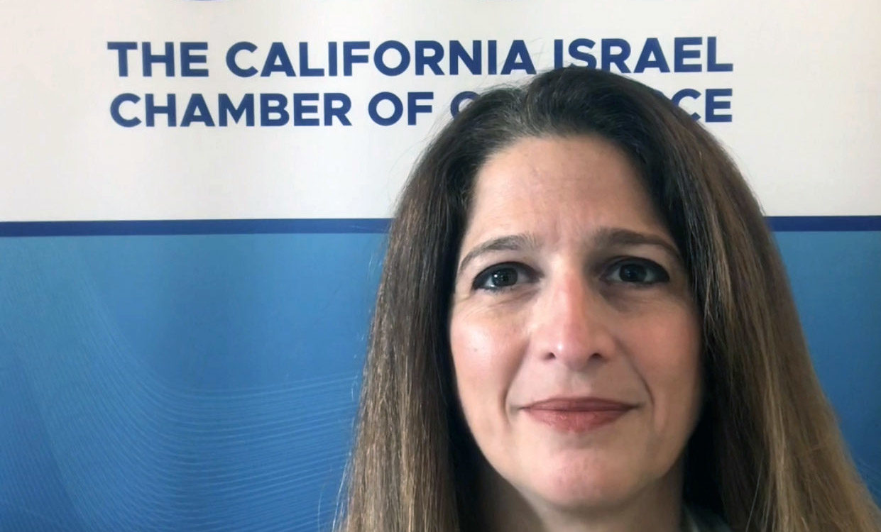 """a woman in front of a sign that says """"California Israel Chamber of Commerce"""""""