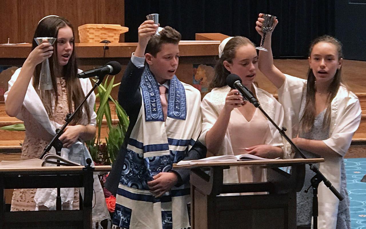 Quadruplets Noa, Nathan, Elie and Emma Friedman-Lowenthal lead kiddush during their joint b'nai mitzvah at Congregation Emanu-El in San Francisco, Nov. 17, 2018