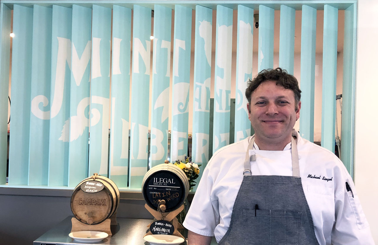"""a smiling man in an apron stands in front of an interior sign that says """"Mint & Liberty"""""""