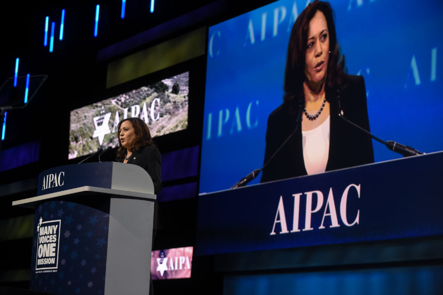 harris on stage speaking at a podium with an AIPAC logo behind her