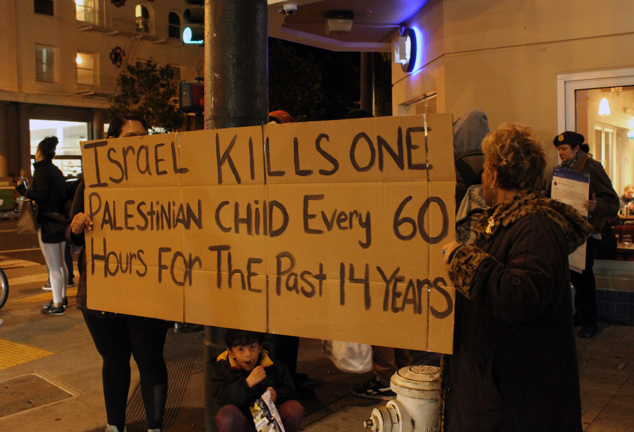 """a group of people, a prominent sign reads: """"Israel kills one Palestinian child every 60 hours for the past 14 years"""""""