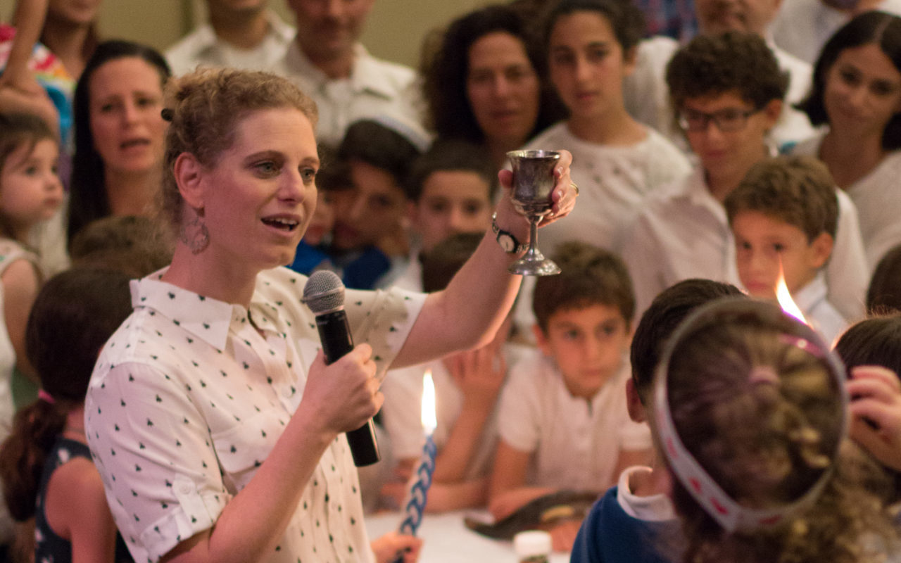 a woman holds up a kiddush cup, speaking to a large crowd