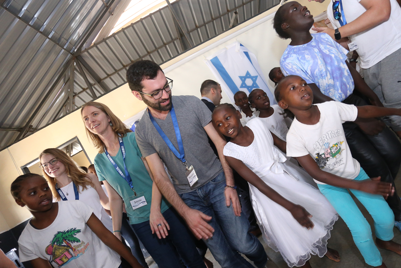 three white people dancing with a crowd of young Kenyan children with an Israeli flag in the background