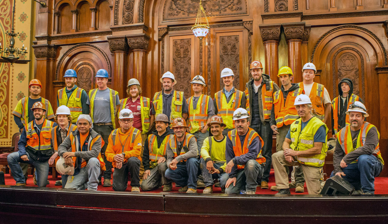 Workers pose for a photo on the bimah of Congregation Sherith Israel after a presentation by congregant Maurice Kamins on the history of the congregation and its historic building. (Photo/Maurice Kamins)