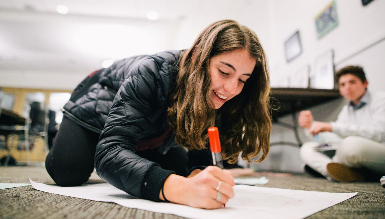 A teen girl writes with a marker, sitting on the floor, smiling