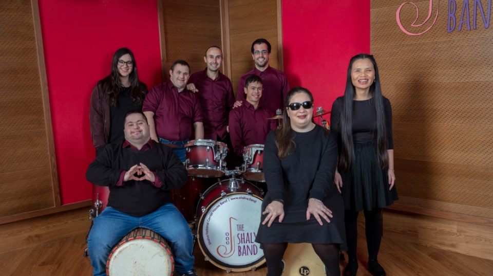 three young women (including two blind lead singers) and five young men stand around a drum set with the Shalva Band logo on it, smiling and posing; a young man with Down syndrome holds his hands up in a heart shape