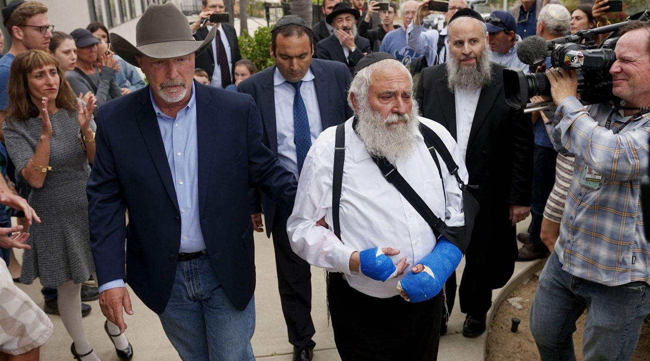Poway Chabad leader Rabbi Yisroel Goldstein, who was shot in the hands, walks towards a press conference with Poway Mayor Steve Vaus, April 28, 2019. (Photo/JTA-Sandy Huffaker-AFP-Getty Images)