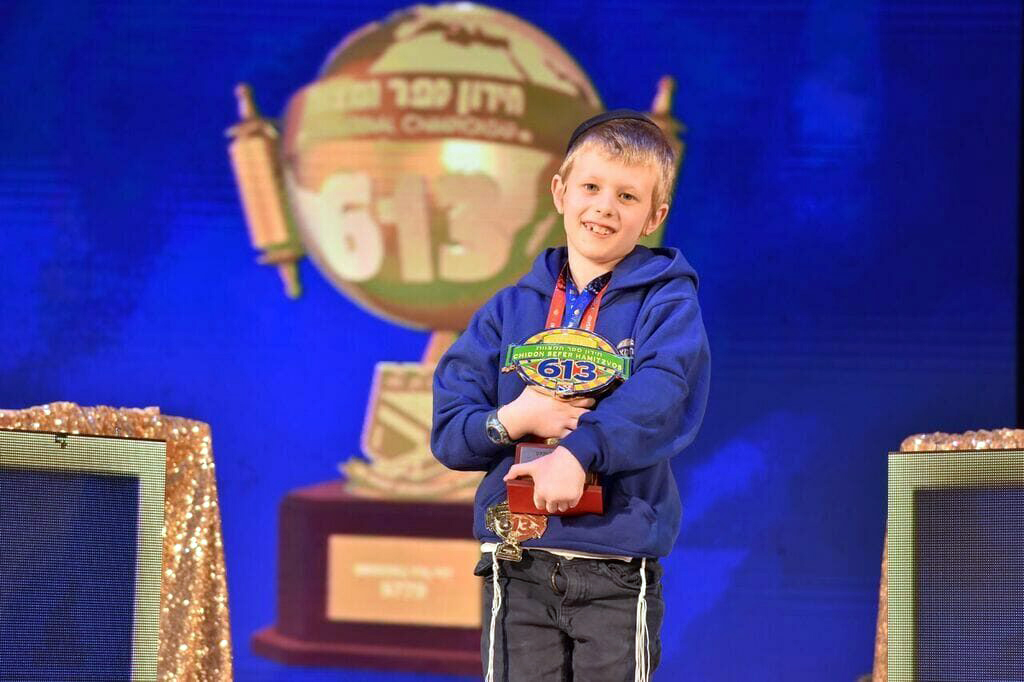 a small young boy in a blue hoodie holds up a trophy