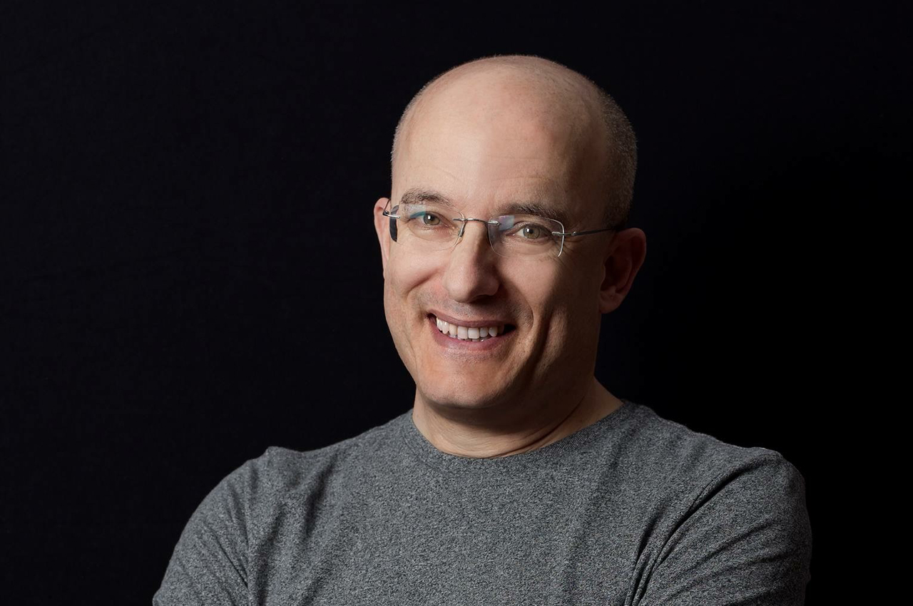 a smiling bald man with glasses