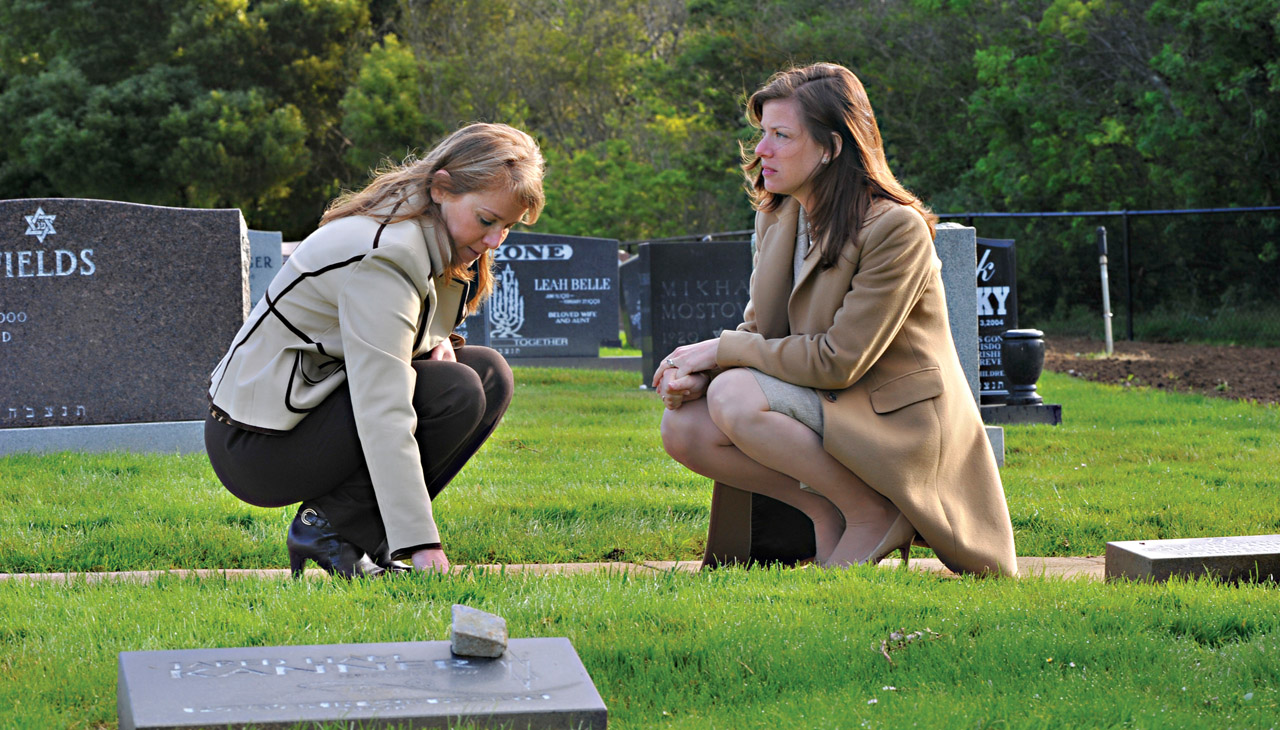 Two women kneel pensively on a path near headstones and open grass