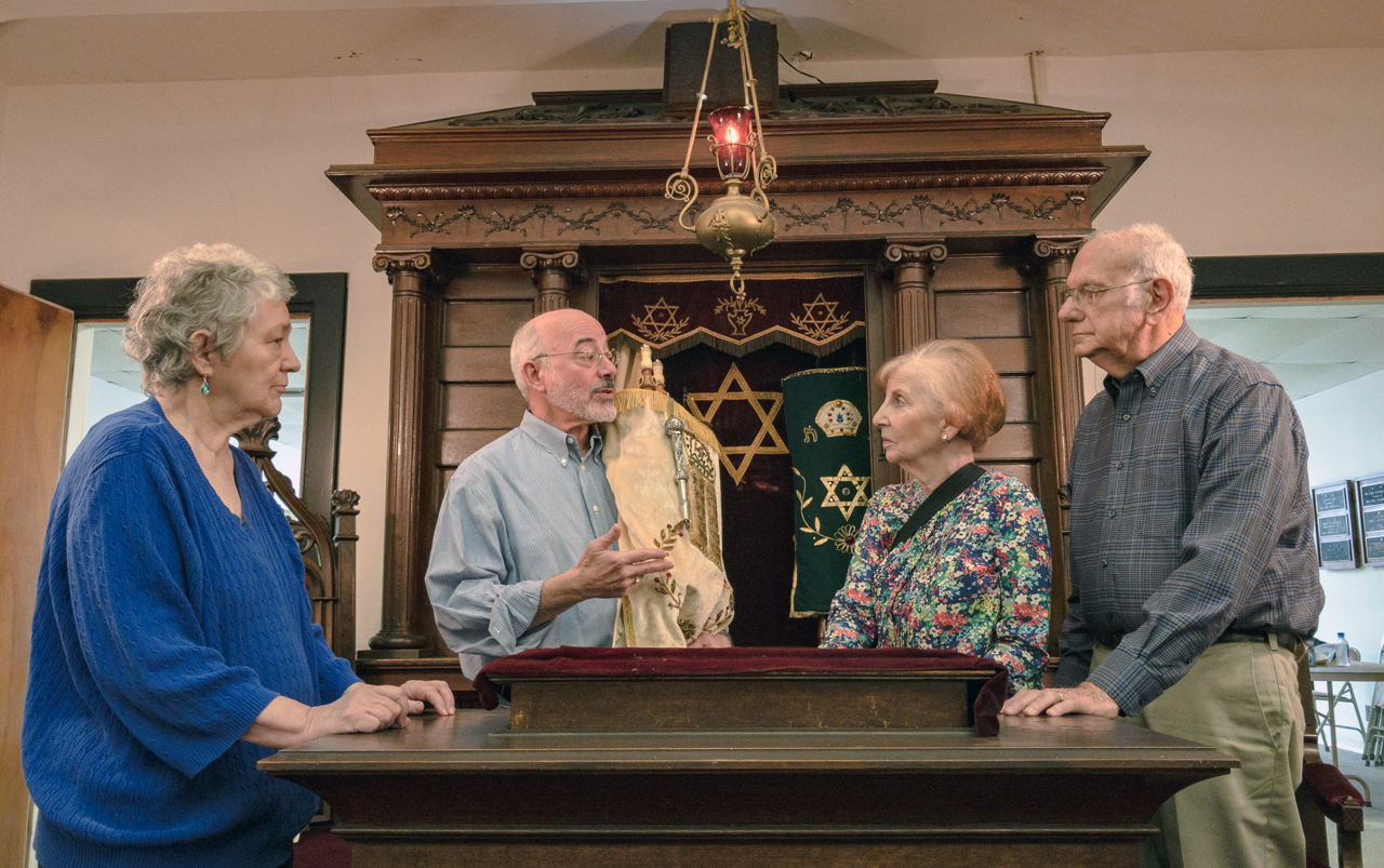 (From left) the four members of Temple Mishkan Israel in Selma, Alabama: Hanna Berger, Ronnie Leet, Joanie Gibian Looney and Charles Pollack — stand in front of the Torah ark. (Photo/JTA-Amy Milligan)
