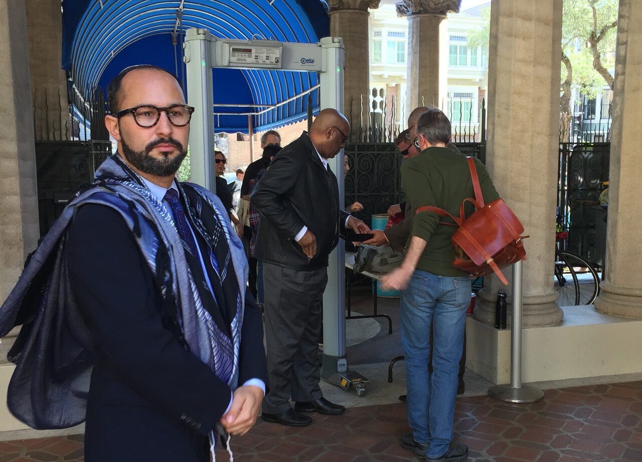 Rabbi Jason Rodich at the entrance to Congregation Emanu-El in San Francisco, which has long used metal detectors and unarmed guards to screen people coming into the building. (Photo/Sue Barnett)