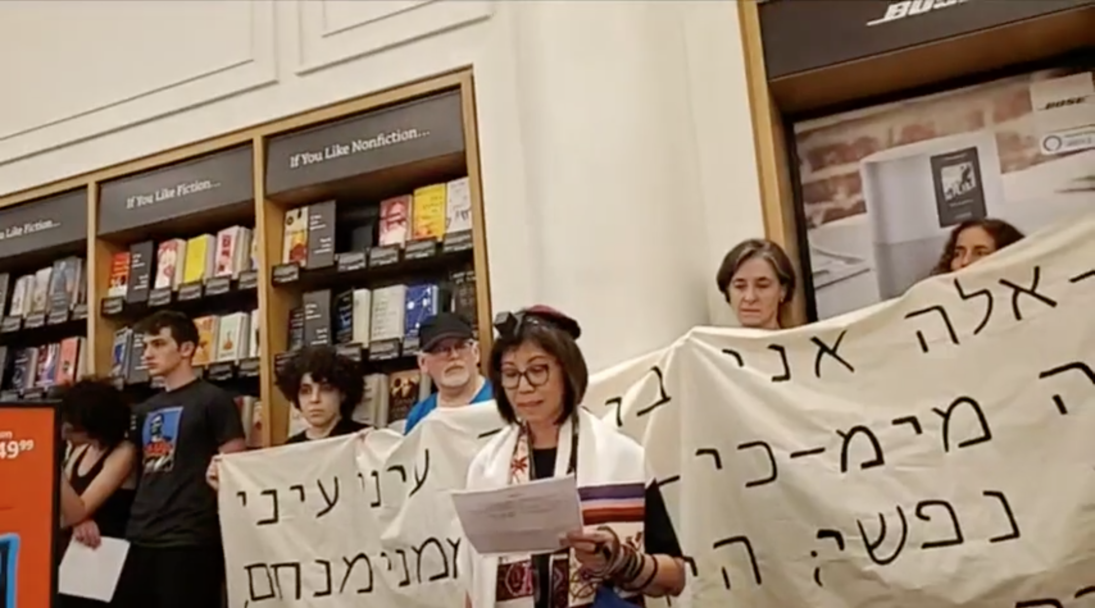 Rabbi Mira Rivera speaks at a Jewish protest against Amazon at one of the company's brick-and-mortar stores in New York City, Aug. 11, 2019. The protest was held on Tisha B'Av, a traditional Jewish day of mourning. Behind the speaker is a banner with a Hebrew quotation from the Book of Lamentations, which is traditionally read on Tisha B'Av. (Photo/JTA-Facebook video screenshot)