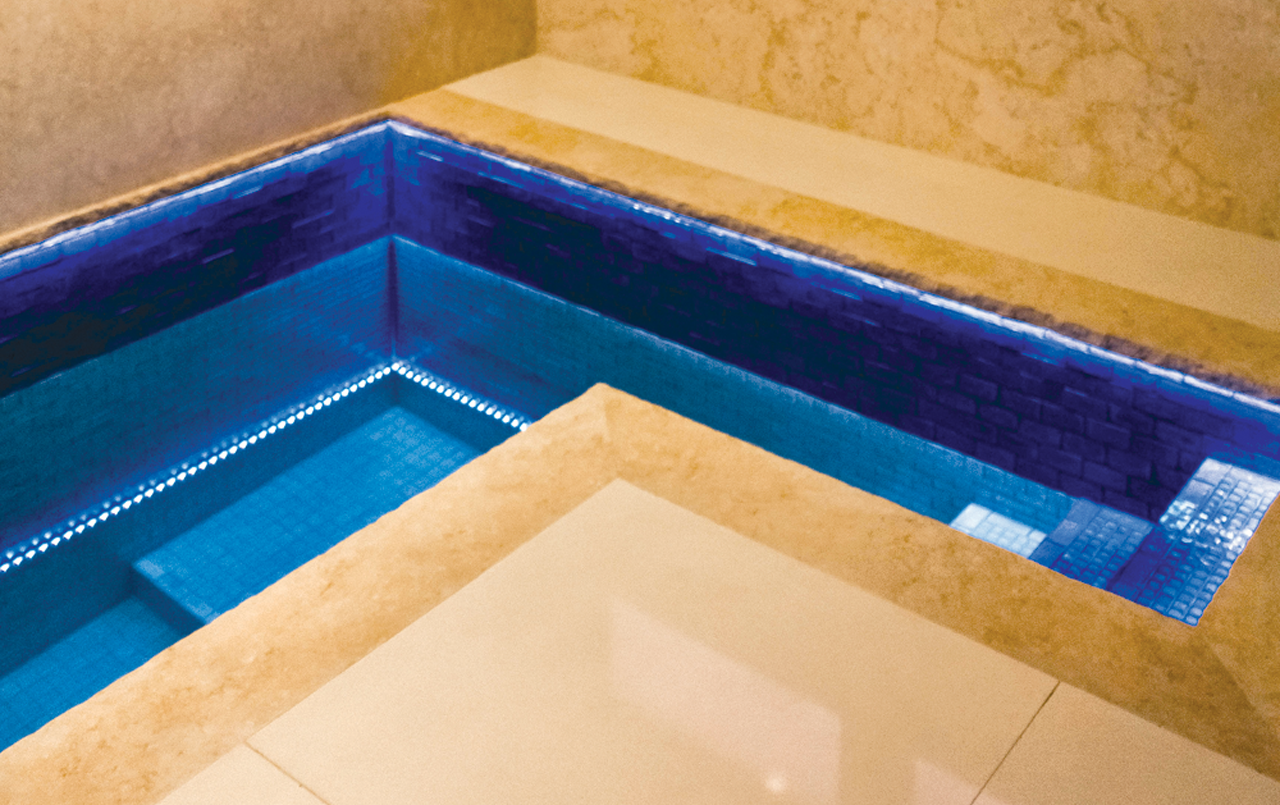 a small, deep blue pool indoor surrounded by marble