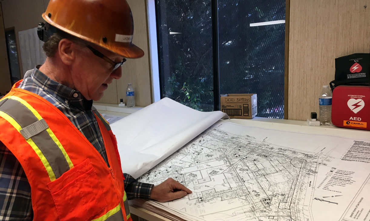 a man in a hard hat examines blueprints