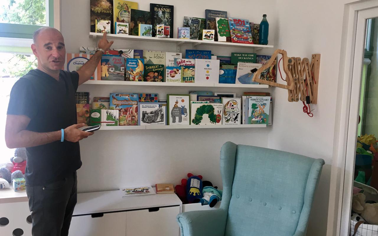 JCC Krakow director Jonathan Ornstein shows off the center's preschool books. (Photo/Gunda Trepp)