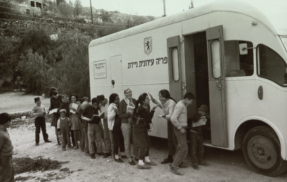 a line of smiling children next to a truck full of books