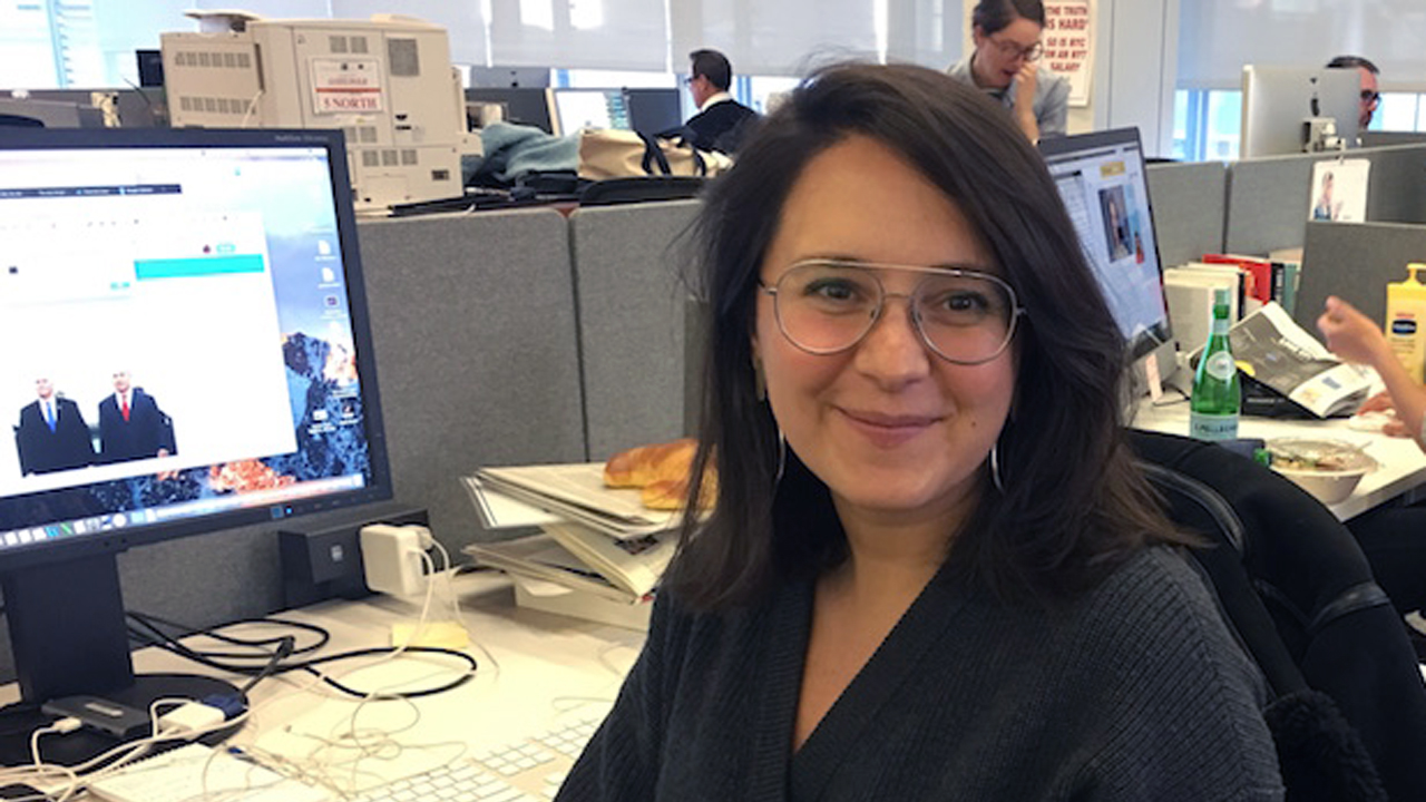 a dark-haired woman in glasses smiles, sitting at a desk
