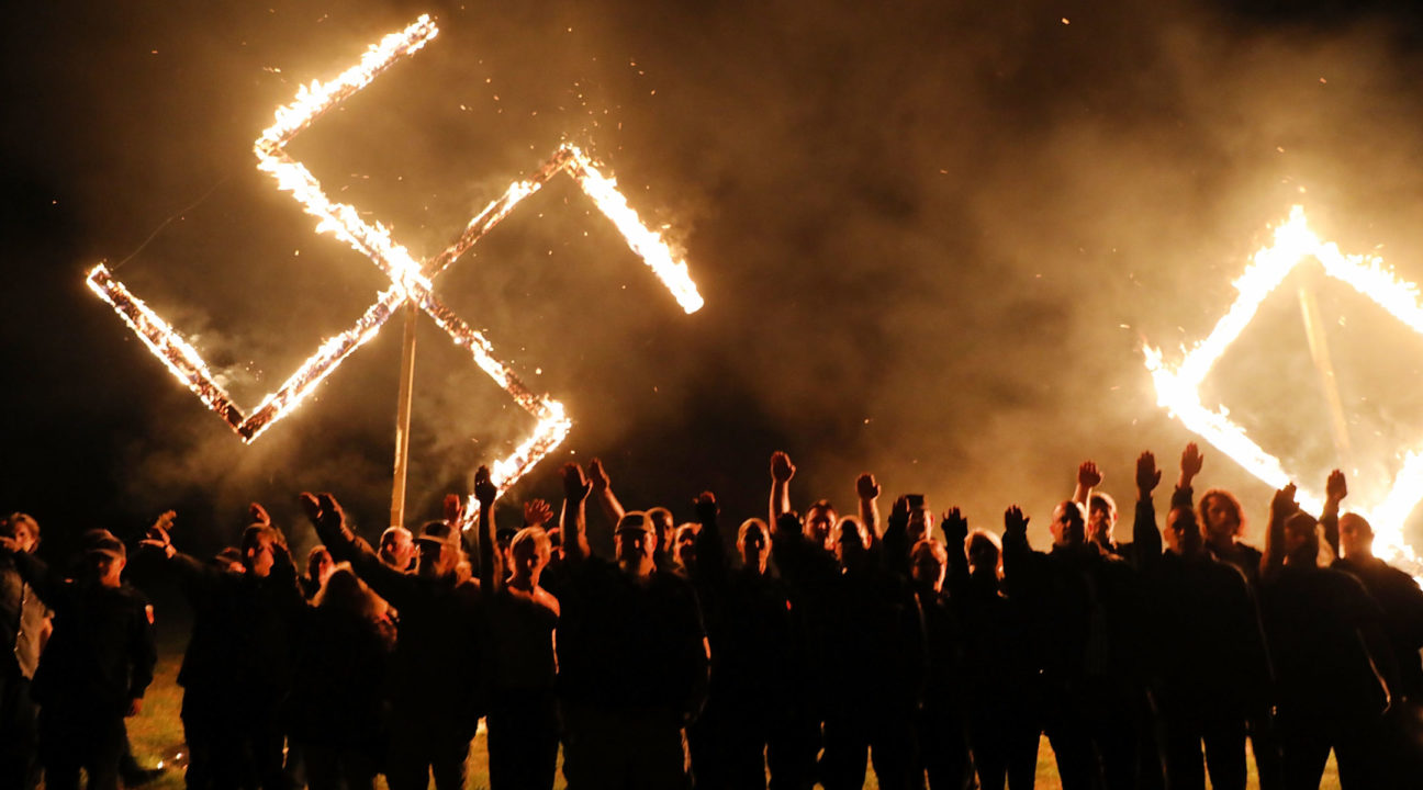 Members of the National Socialist Movement, one of the largest neo-Nazi groups in the US, hold a swastika burning after a rally on April 21, 2018 in Draketown, Georgia. /JTA-Spencer Platt-Getty Images