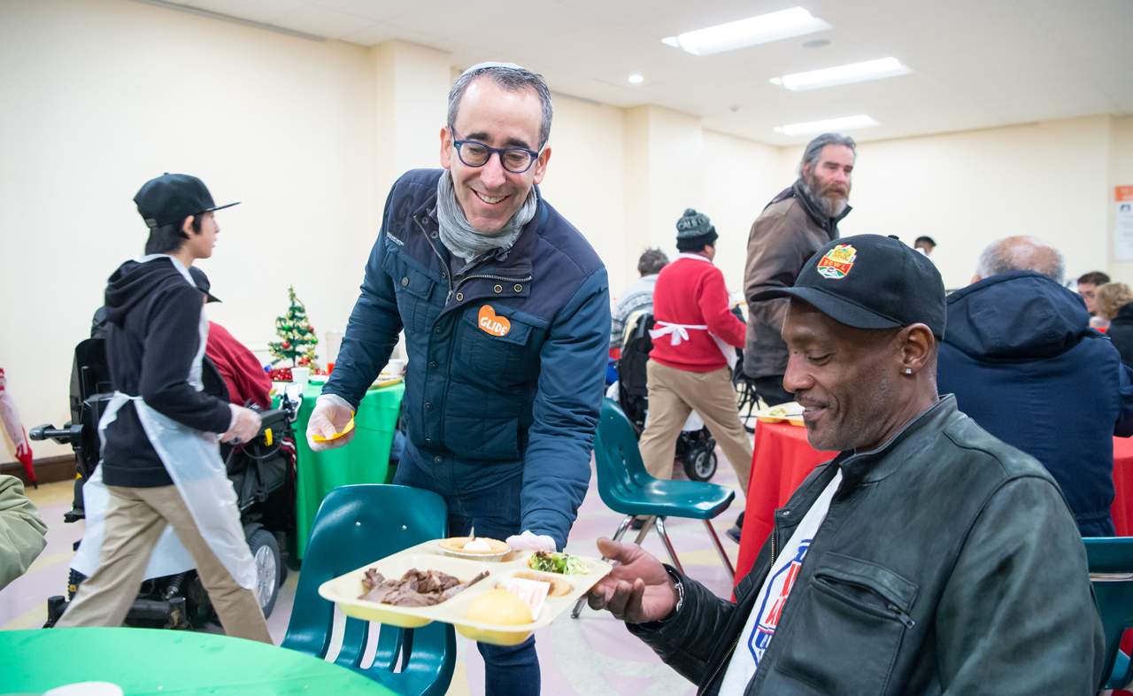 Rabbi Michael Lezak serving a guest at one of Glide's daily free meals. /Alain McLaughlin