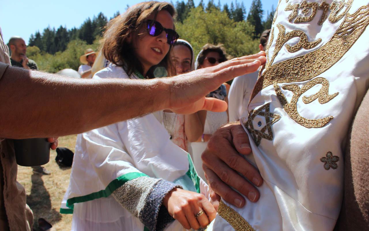 Worshippers reach for the Torah during services at Wilderness Torah's Rosh Hashanah retreat. (Photo/Gabriel Greschler)