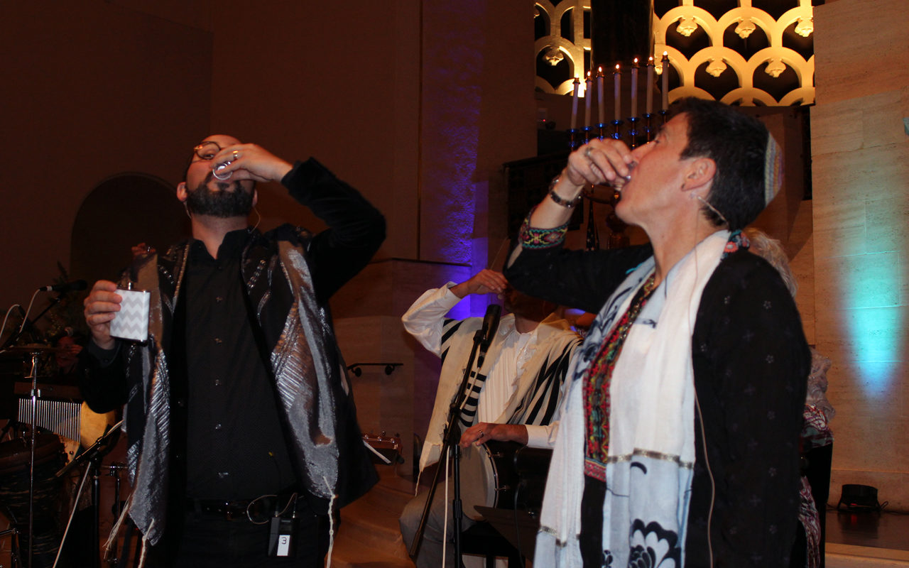 """Rabbis Jason Rodich and Sydney Mintz toast the 20th anniversary of Congregation Emanu-El's """"Late Shabbat"""" with shots of tequila on the bimah, Nov. 9, 2019. (Gabe Stutman)"""