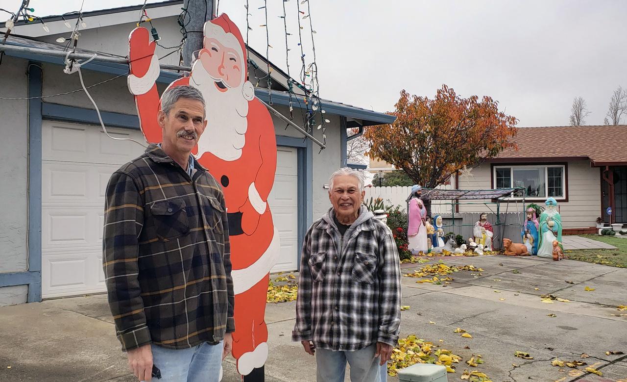 Neighbors Martin Gewing (left) and Ben Marin with Marin's venerable streetside Santa display.