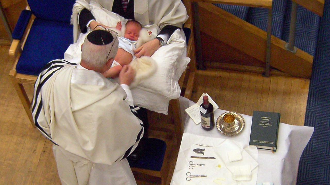 A mohel performs a circumcision during a bris (or brit milah) ceremony. (Cheskel Dovid/Wikimedia CC BY 3.0)