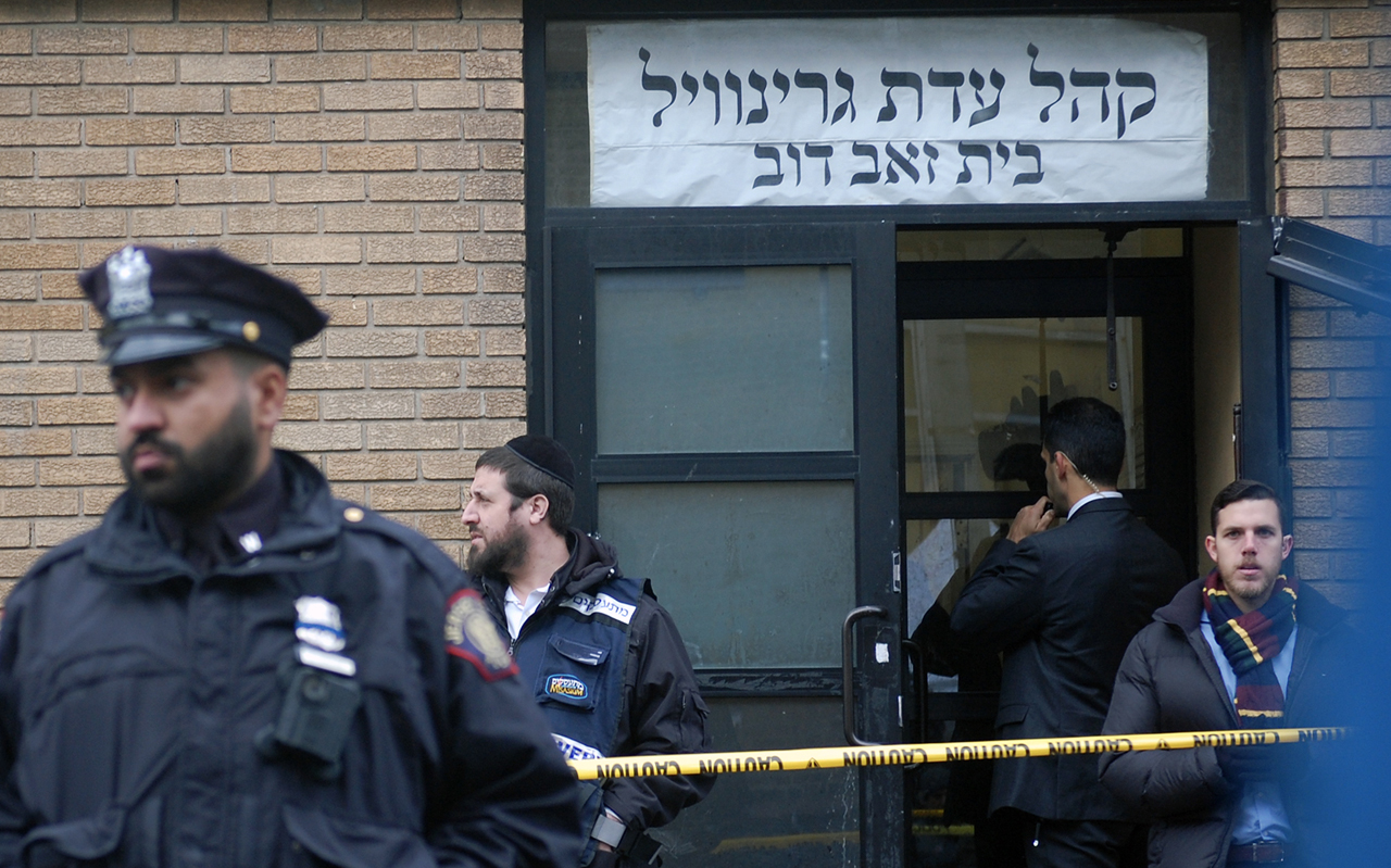Hasidic Jews, government officials and police officers stand in front of the K'hal Adas Greenville synagogue next door to the JC Kosher Supermarket in Jersey City, N.J., the site of a deadly shooting, Dec. 11, 2019. (JTA/Laura E. Adkins)