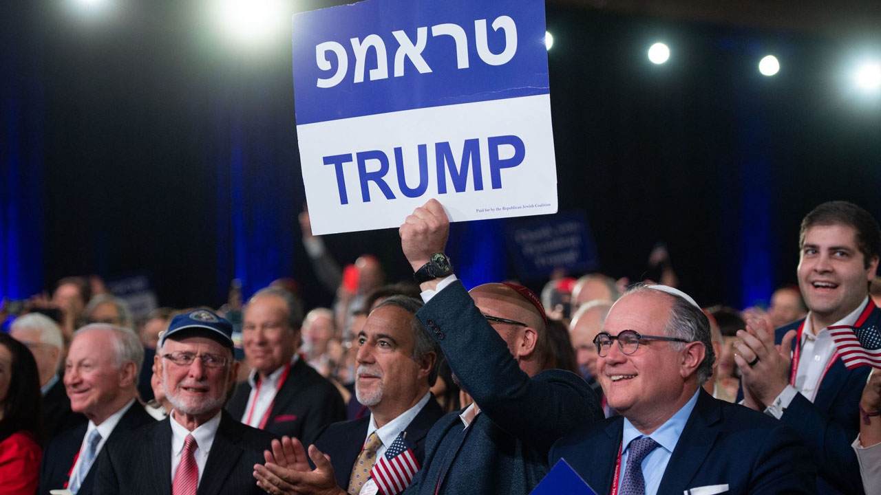 Supporters of Donald Trump hold signs in Hebrew and English as the president speaks at the Republican Jewish Coalition's annual leadership meeting in Las Vegas, April 6, 2019. (JTA/Saul Loeb/AFP via Getty Images)