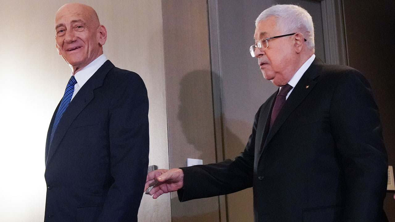 Former Israeli Prime Minister Ehud Olmert, left, and Palestinian Authority President Mahmoud Abbas arrive for a news conference in New York on President Donald Trump's Israeli-Palestinian peace plan, Feb. 11, 2020. (JTA/Bryan R. Smith/Getty Images)