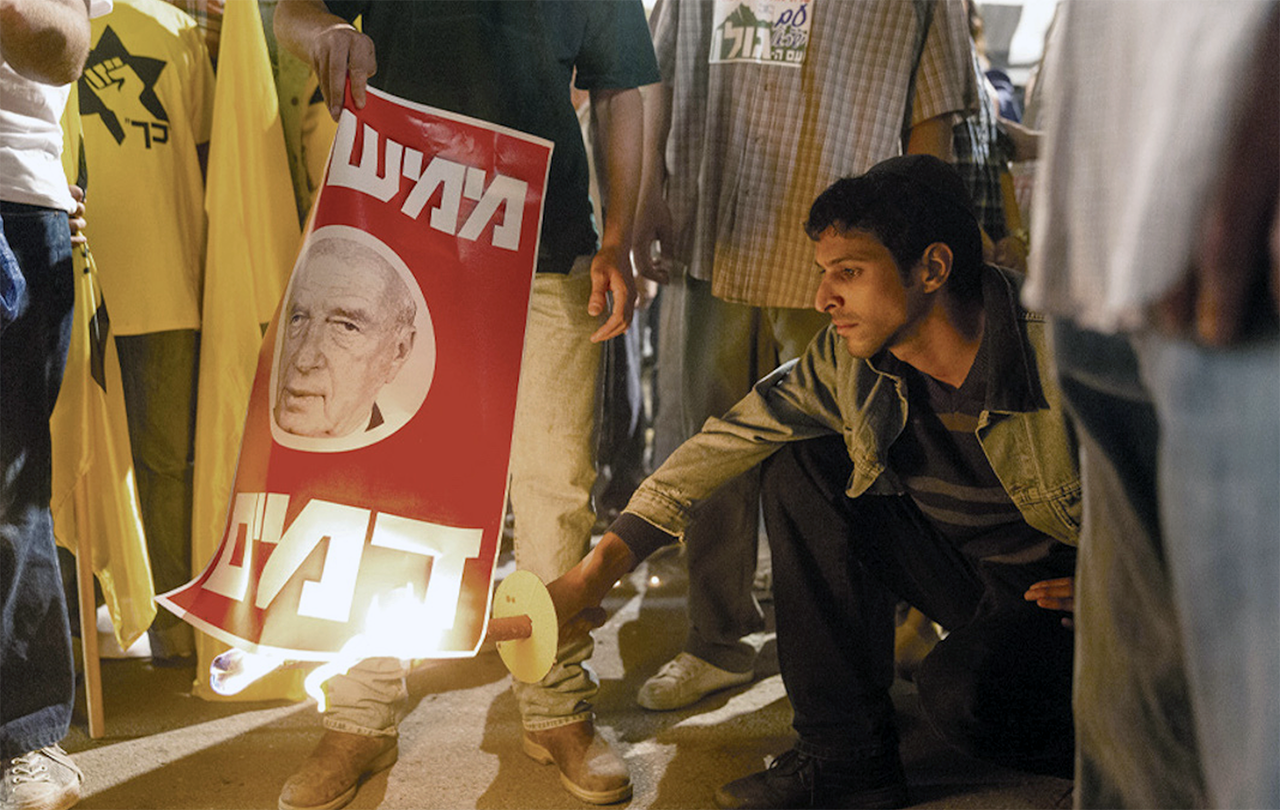 "Yigal Amir (Yehuda Nahari Halev) torches a poster of Prime Minister Yitzhak Rabin in ""Incitement."""