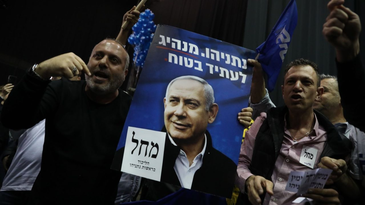 Likud supporters displaying a poster of Prime Minister Benjamin Netanyahu celebrate at party headquarters in Tel Aviv following the release of the first exit polls showing their party on top, March 2, 2020. (JTa/Olivier Fitoussi/Flash90 )