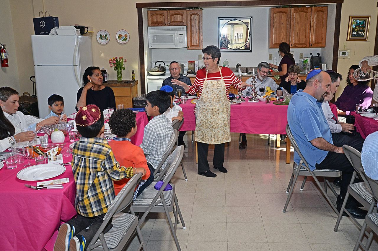 Doreen Alper (center, in the matzah apron) sometimes has 60 or more people at her seders, such as this one in 2015. This year, she's facing the prospect of a much smaller gathering. (EDWARD LECHTZIN)