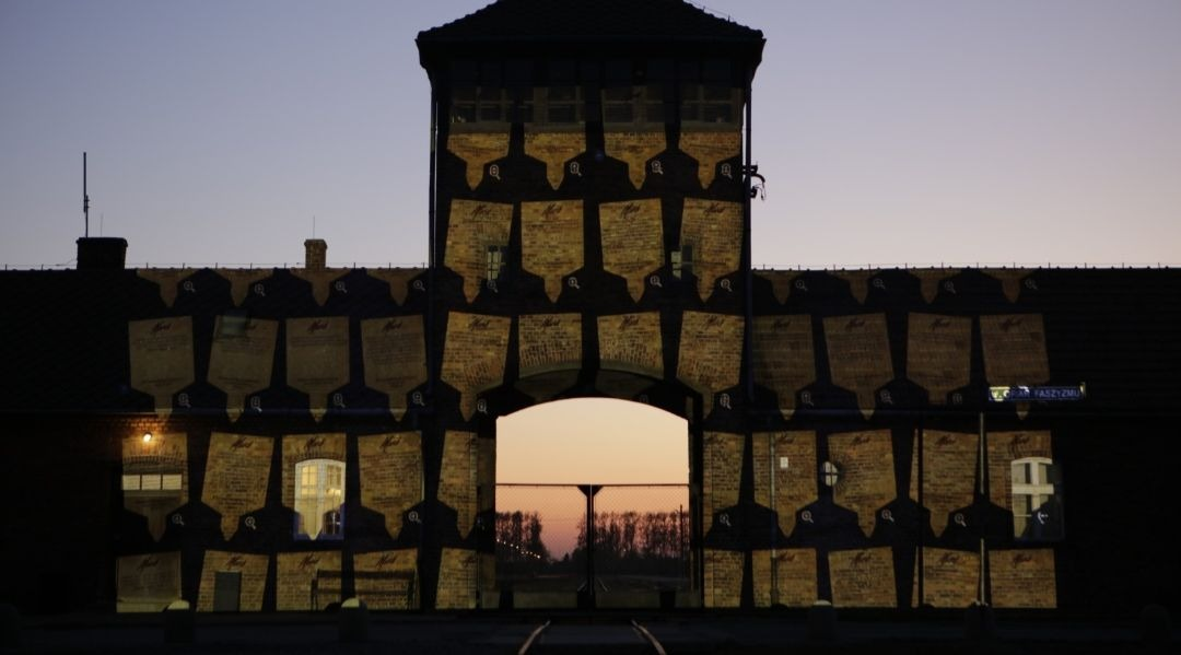 Virtual memorial plaques are projected on the gates of Auschwitz-Birkenau for Holocaust Remembrance Day, 2020. (Photo/JTA-Marcin Kozlowski-March of the Living)
