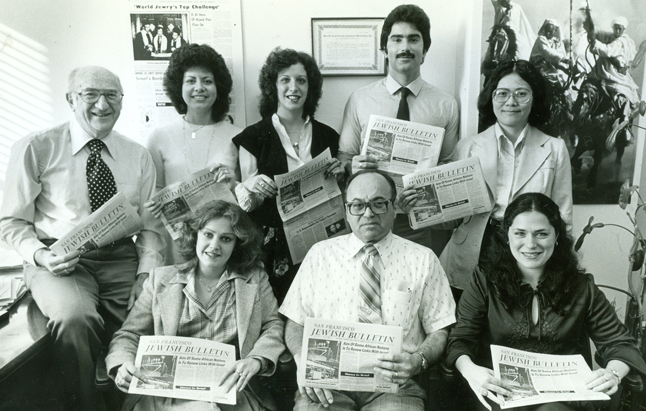 The staff of the Jewish Bulletin (J.'s former name) in 1980: managing editor Geoffrey Fisher (top row, left), assistant editor Phil Bronstein (top row, second from right) and ad manager Charles Block (front row), with colleagues (clockwise, from top left) Brunhilda Sierra, Peggy Isaak, Mary Fong, Marjorie Glazer and Nancy Royfe.