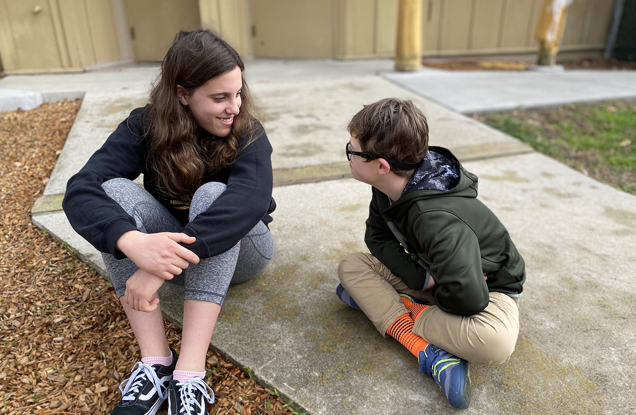 Friendship Circle volunteer Jamie Sloves, 14, with her buddy Ben Kramer, 11, taking some quiet time on the playground. (COURTESY FRIENDSHIP CIRCLE)