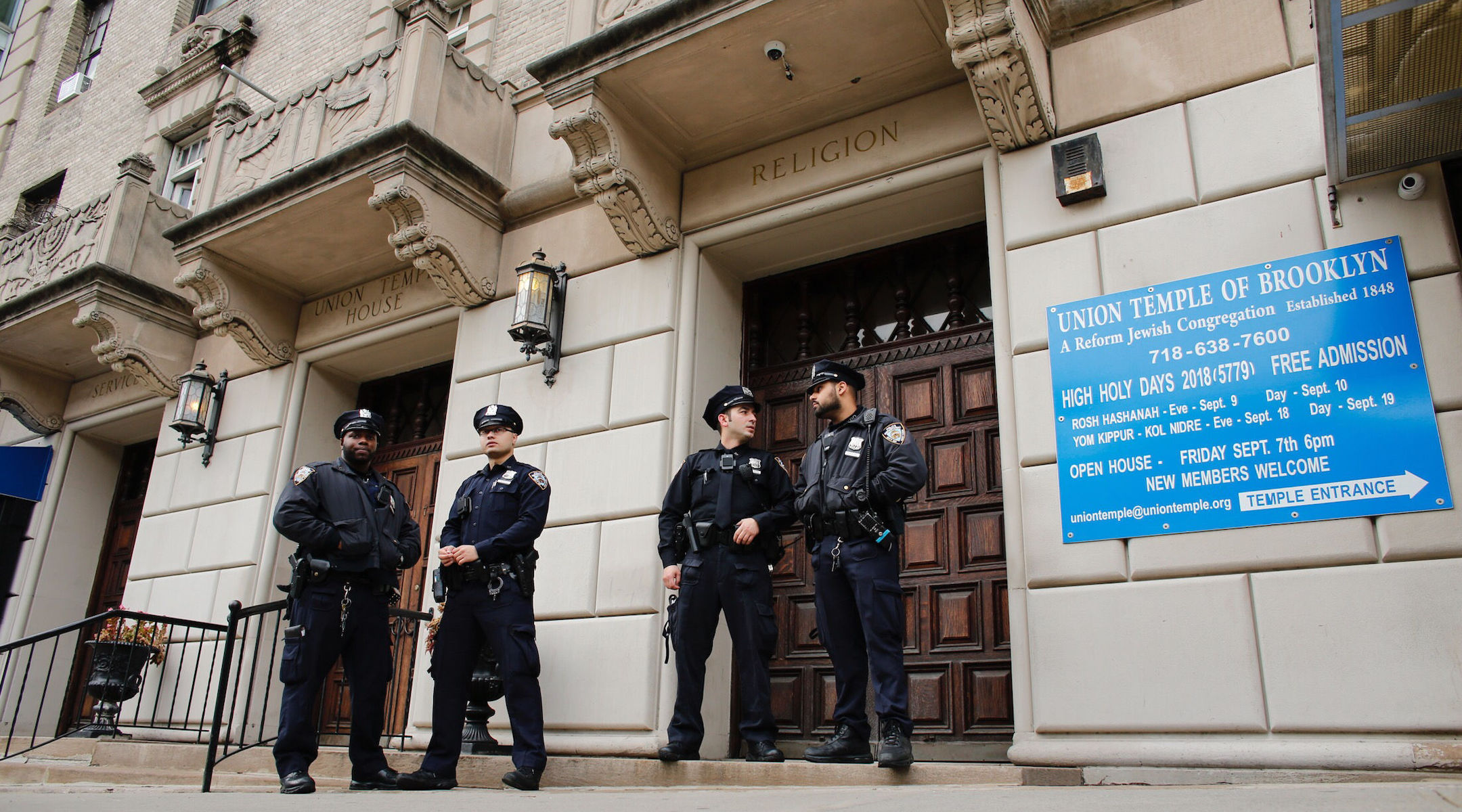 New York police officers stand guard at the door of the Union Temple of Brooklyn after it was vandalized with graffiti, Nov. 2, 2018. (Photo/JTA-Kena Betancur-AFP via Getty Images)