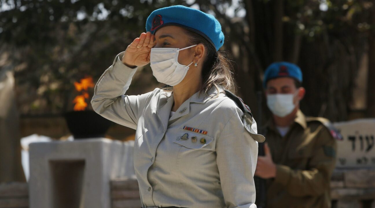 Israeli soldiers, wearing mandatory protective masks due to the Covid-19 coronavirus pandemic, pay tribute to fallen soldiers at the Kiryat Shemona military cemetery in northern Israel, April 28, 2020. (Photo/JTA-Jalaa Marey-AFP via Getty Images)