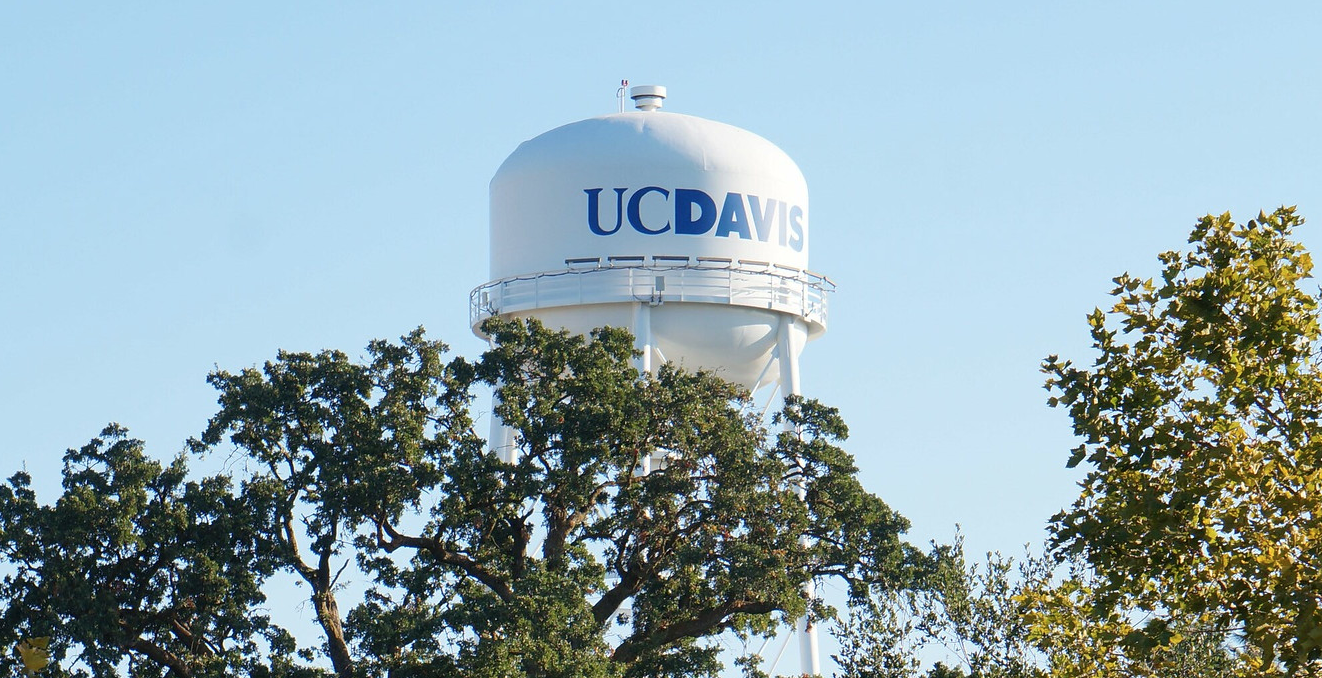 a water tower that says UC Davis in blue writing