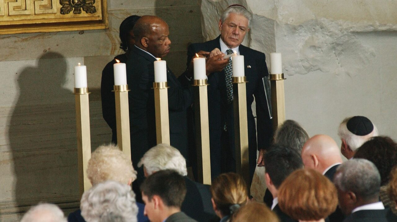 Black man and elderly white Jewish man light Holocaust memorial candle in front of audience at U.S. Capitol building.