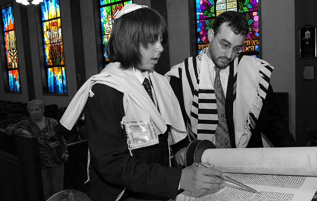 a boy in a talit reads from the Torah while a man in a talit stands next to him