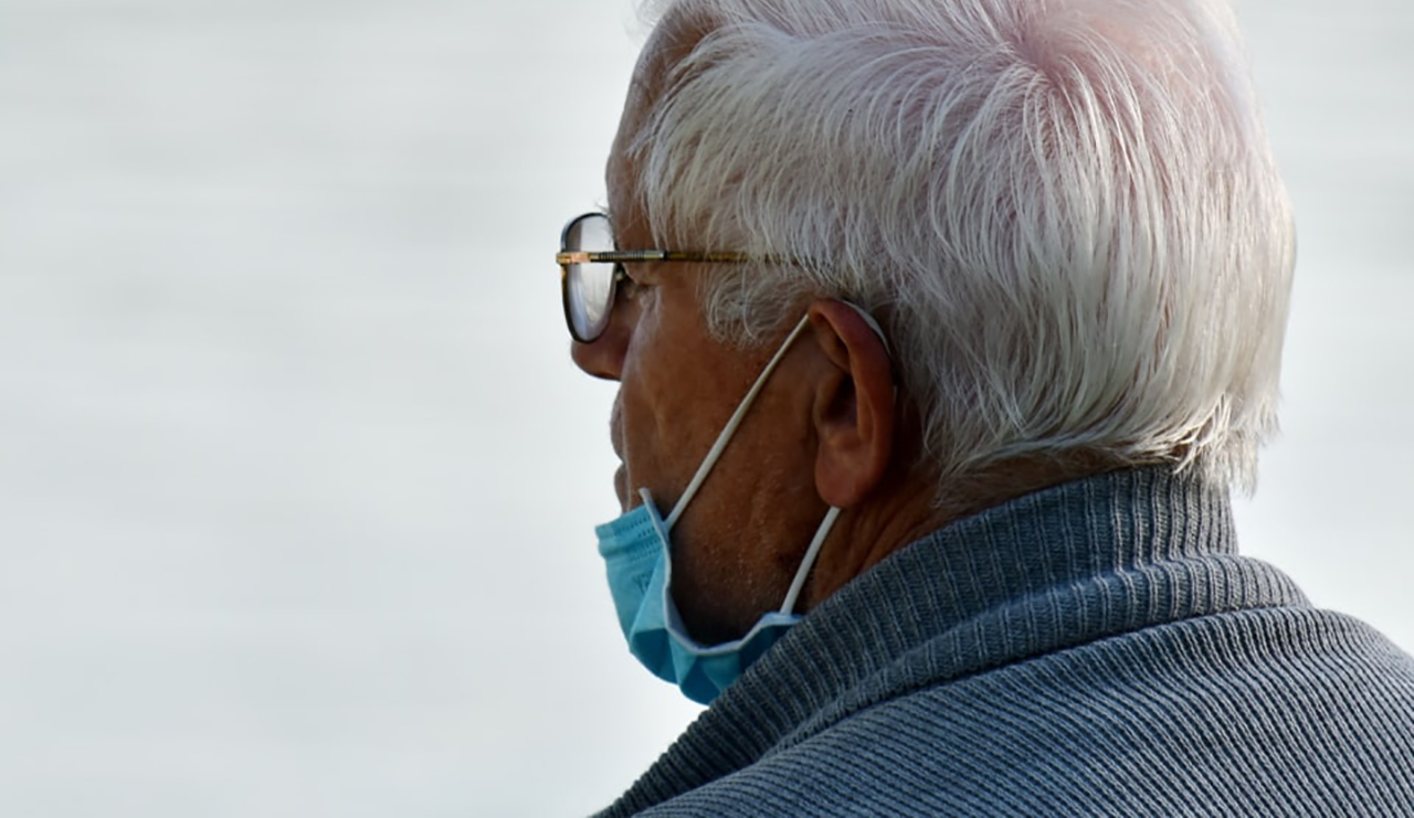 an old man wearing a blue face mask