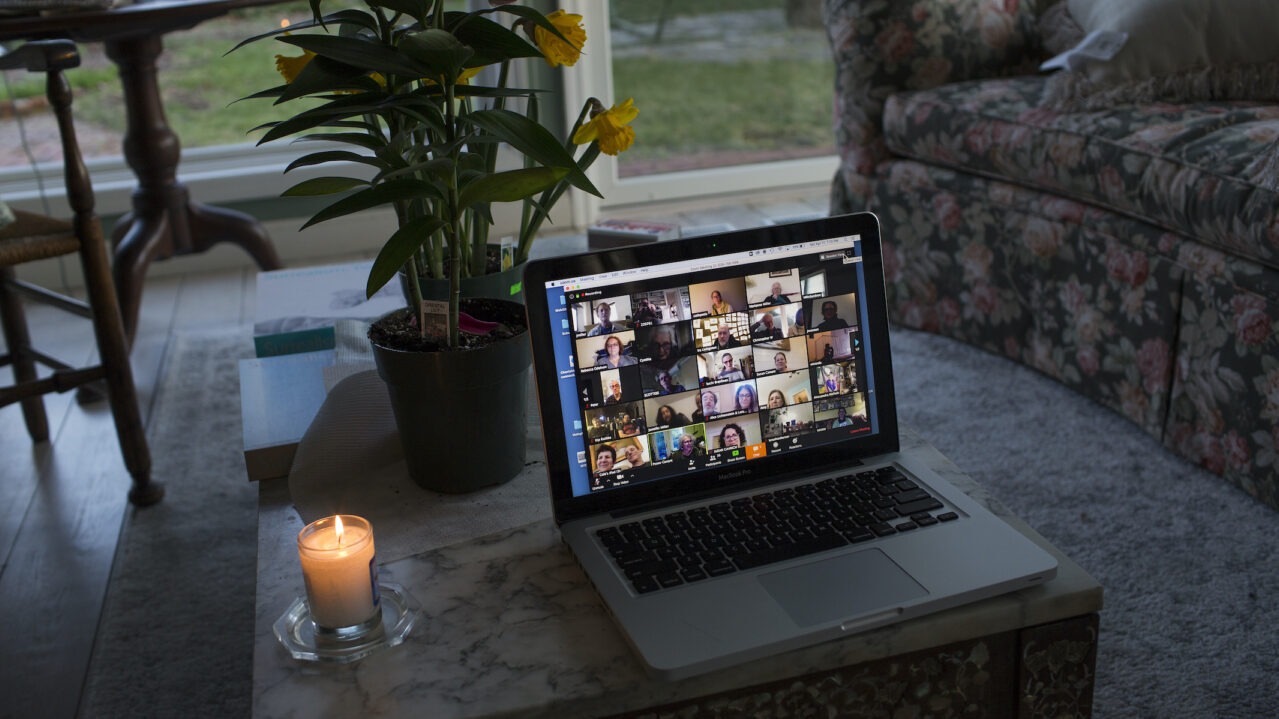 A laptop with Zoom open on it next to a lit yahrzeit candle