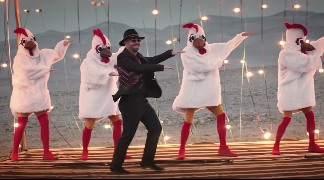 a man in a fedora dances with four people in cartoonish rooster costumes