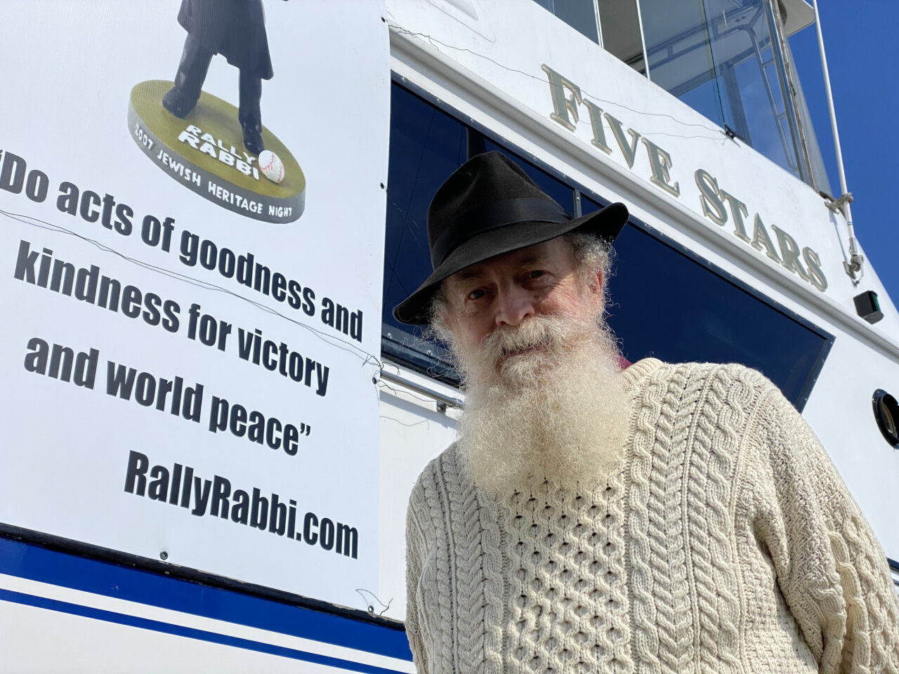 """A man with a long beard, black hat and cableknit sweater stands on the deck of a yacht with a """"Rally Rabbi"""" sign behind him"""